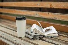 Ein Buch und ein Glas Kaffee im Park auf einer Bank stockbilder