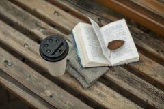 Ein Buch und ein Glas Kaffee im Park auf einer Bank stockbild