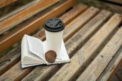 Ein Buch und ein Glas Kaffee im Park auf einer Bank lizenzfreies stockbild
