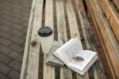 Ein Buch und ein Glas Kaffee im Park auf einer Bank lizenzfreie stockfotografie
