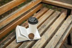 Ein Buch und ein Glas Kaffee im Park auf einer Bank lizenzfreie stockbilder