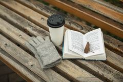 Ein Buch und ein Glas Kaffee im Park auf einer Bank stockfotos