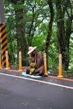 Ein buddhistischer Mönch, der an der Straße in Taiwan-Dschungel sitzt stockfotografie