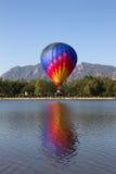 Ein bunter Heißluftballon, der in einen See eintaucht stockbild