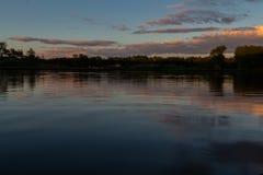 Ein bunter Sonnenuntergang mit Reflexionen in einem See in Bokrijk, Belgien mit einem drastischen Himmel lizenzfreie stockfotos