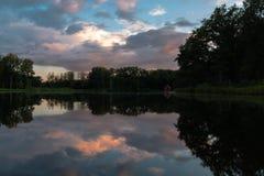 Ein bunter Sonnenuntergang mit Reflexionen in einem See in Borkijk, Belgien stockbild