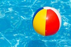Ein bunter Wasserball, der in einen Swimmingpool schwimmt Stockfotos