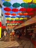 Ein buntes Foto von Regenschirmen in einem Einkaufssäulengang Stockfoto
