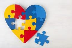 Ein buntes Herz, das vom symbolischen Autismuspuzzlespiel gemacht wird, bessert aus Stockbild