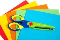 Ein buntes Plastikkind scissor auf Papier Lizenzfreies Stockfoto