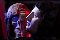 Ein buntes Stillleben eines künstlichen Schädels und der weiblichen Gesichtsstatue Stockbild