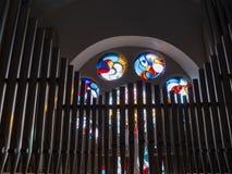 Ein Buntglas stieg Fenster hinter die Orgelpfeifen der Pfeifenorgel in der Kirche von Wilwerdange, Luxemburg stockbild