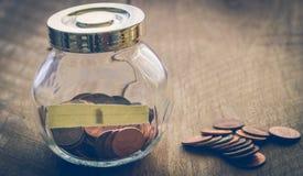 Ein Cent prägt auf Holztisch und in Glasgefäßweinlese-Farbst. Stockbild