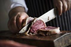 Ein Chef, der an dem Schneiden eines Stückes der Steaklebensmittelphotographie-Rezeptidee arbeitet Stockfotografie