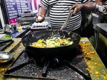 Ein Chef, der tadka Fischrogen in einer Bratpfanne an einer Straßenseiten-Nahrungsmittelecke auf einem Ofen über Flammen kocht lizenzfreies stockbild