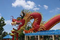 Ein chinesischer roter Drache mit dem gelockten Schnurrbart, der über dem Dach klettert Lizenzfreie Stockfotos
