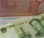 Ein chinesischer Yuan ist auf einem Pass mit einem chinesischen Visum und Grenzstempeln lizenzfreie stockfotos