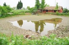 Ein chinesisches Dorfhäuschen und ein getrockneter Teich Lizenzfreies Stockfoto