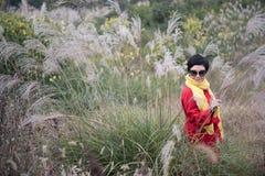 Ein chinesisches Mädchen-Schießen in Miscanthus-Hintergrund Lizenzfreies Stockbild