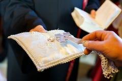 Ein christlicher Priester hält in seinen Händen einen Ehering stockbild