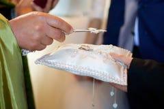 Ein christlicher Priester hält in seinen Händen einen Ehering lizenzfreie stockfotografie