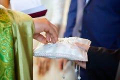 Ein christlicher Priester hält in seinen Händen einen Ehering stockfotografie