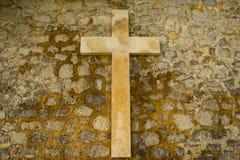 Ein christliches Kreuz auf einer Steinwand lizenzfreie stockfotografie