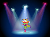 Ein Clowntanzen über dem Ball mit Scheinwerfern Stockfotos