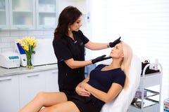 Ein Cosmetologist hält Hände und vor der Ausführung von Verfahren überprüft das Gesicht einer Frau Das Mädchen an der Aufnahme an lizenzfreies stockfoto