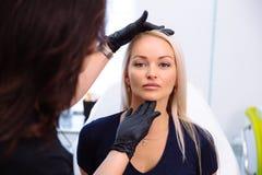 Ein Cosmetologist hält Hände und vor der Ausführung von Verfahren überprüft das Gesicht einer Frau Das Mädchen an der Aufnahme an stockfoto