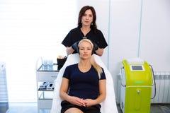 Ein Cosmetologist hält Hände und vor der Ausführung von Verfahren überprüft das Gesicht einer Frau Das Mädchen an der Aufnahme an lizenzfreie stockfotografie