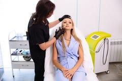Ein Cosmetologist hält Hände und vor der Ausführung von Verfahren überprüft das Gesicht einer Frau Das Mädchen an der Aufnahme an stockfotografie
