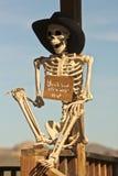 Ein Cowboy Skeleton Sits Against ein Beitrag Stockbild