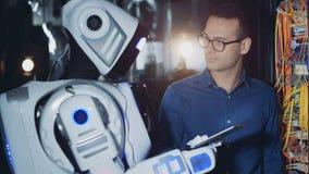 Ein Cyborg gibt einem Mann eine Tablette in einem Serverraum, Abschluss auf stock footage