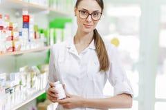 Ein dünnes schönes Mädchen einen Laborkittel tragend, zeigt ein kleines Glas zur Kamera in einer modernen Apotheke lizenzfreie stockbilder