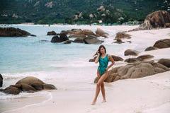 Ein dünnes, suntanned junges Mädchen in der aquamarinen Spule steht auf dem Strand, auf einem weißen sandigen Strand mit den Fels Lizenzfreies Stockfoto