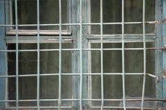 Ein düsteres Fenster mit einem Gitter in einer Betonmauer stockbild