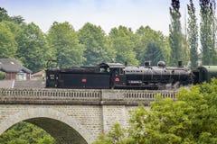 ein Dampfzug, der eine Brücke in St Leonard de Noblat, Frankreich kreuzt Stockbilder