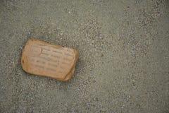 Ein defekter Ziegelstein auf dem Strand Stockfotografie