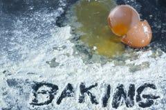 Ein defektes Ei auf einer Oberfläche umfasst im Mehl mit dem Wort Lizenzfreie Stockfotos