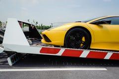 Ein defektes Fahrzeug unten gegurtet zur Plattform des Flachbettabschleppwagens lizenzfreies stockfoto