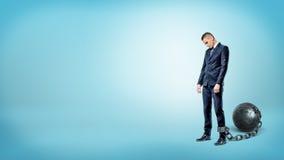 Ein deprimierter Geschäftsmann auf blauem Hintergrund steht mit einem gesenkten Kopf, während er an einen Eisenball angekettet wi Stockfoto