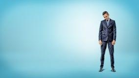 Ein deprimierter Geschäftsmann, der mit Schultern steht, stürzte auf blauem Hintergrund Stockfotografie