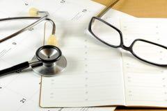 Ein Desktop mit Stethoskop, Adressbuch, Gläsern und Kalender Stockbild