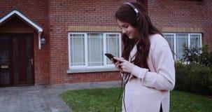 Ein Detail von weiblichen Beinen in den Rollen auf städtischer Straße Junges Mädchen, das auf Smartphone vor Haus und Auto simst stock footage
