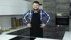 Ein dicker Mann in einem Schutzblech steht mitten in der Küche lächelnd mit den Händen auf seinen Seiten Ein Stoutkerl in einem S stock footage