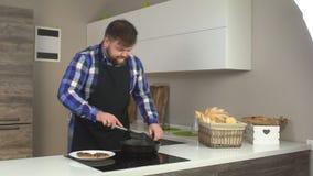 Ein dicker Mann mit einem Bart in der Küche schnüffelt den Geruch von gebratenen frischen Koteletts, langsames MO stock video footage
