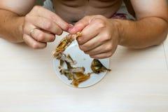 Ein dicker Mann mit einem nackten Torso isst Fische Stockbilder
