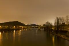 Ein die Moldau-Fluss in Prag mit einer Zugbrücke, die es nachts kreuzt lizenzfreie stockfotos