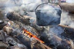 Ein dixy auf dem Feuer ist auf Steinen im Wald Lizenzfreies Stockfoto